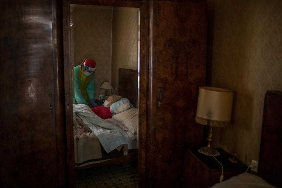 """Josefa Ribas, 86, who is bedridden and suffers from dementia, is attended to by nurse Laura Valdes during a home care visit in Barcelona, Spain, April 7, 2020. Ribas' husband, Jose Marcos, fears what will happen if the virus enters their home and infects them. """"I survived the post-war period (of mass hunger). I hope I survive this pandemic,"""" he said. (AP Photo/Emilio Morenatti)"""