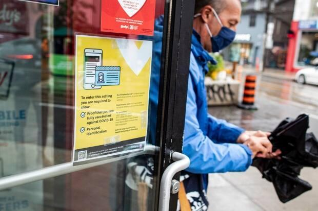 A patron leaves a fast food restaurant on Queen Street in Toronto, past a sign outlining proof of vaccination requirements on Sept. 22. Patrons of dine-in restaurants, nightclubs, gyms, sports facilities and other venues must present a receipt of full vaccination along with government identification. (Evan Mitsui/CBC - image credit)