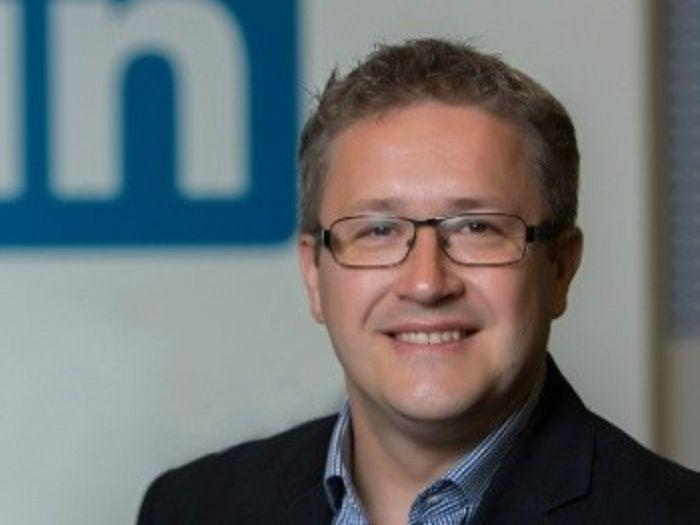 A man wearing a jacket standing in front of the LinkedIn in logo