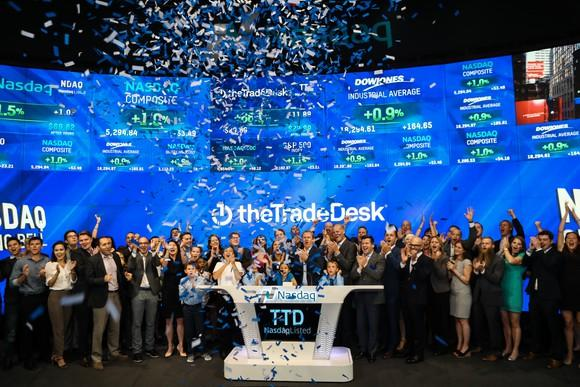 People cheering and waving as confetti rains down, as The Trade Desk Executives ring the NASDAQ opening bell for its IPO.