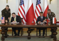 US Secretary of State Mike Pompeo, left, and Poland's Minister of Defence Mariusz Blaszczak sign the US-Poland Enhanced Defence Cooperation Agreement in the Presidential Palace in Warsaw, Poland, Saturday Aug. 15, 2020. Pompeo is on a five day visit to central Europe. (Janek Skarzynski/Pool via AP)