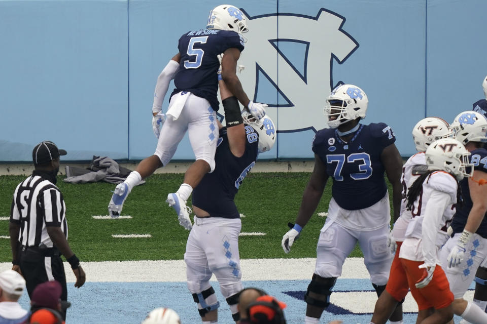 North Carolina offensive lineman Brian Anderson (68) lifts wide receiver Dazz Newsome (5) following Newsome's touchdown against Virginia Tech during the second half of an NCAA college football game in Chapel Hill, N.C., Saturday, Oct. 10, 2020. (AP Photo/Gerry Broome)