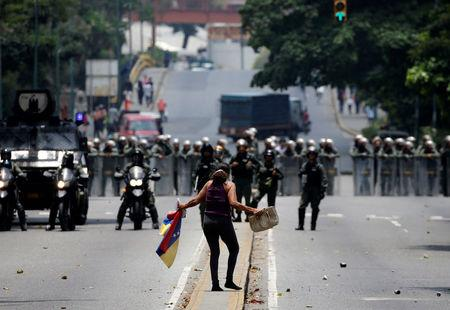 A demonstrator gestures while facing riot police during a rally against Venezuela's President Nicolas Maduro in Caracas
