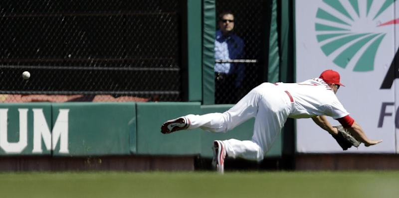 St. Louis Cardinals left fielder Matt Holliday dives but cannot catch a ball hit for a triple by Cincinnati Reds' Billy Hamilton during the first inning of a baseball game Wednesday, April 9, 2014, in St. Louis. (AP Photo/Jeff Roberson)