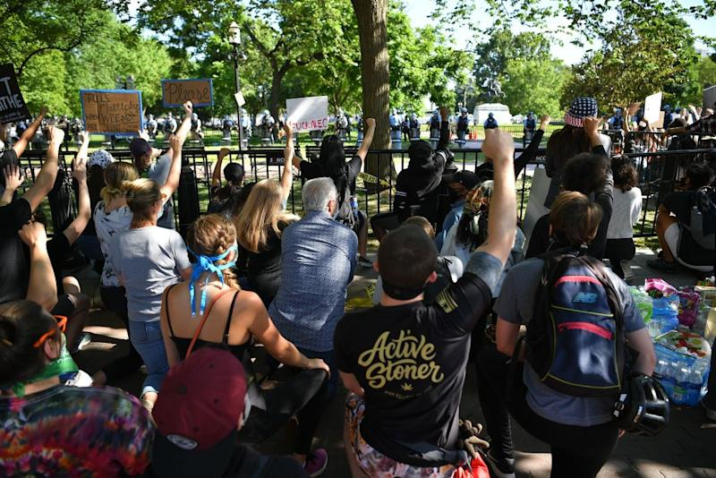 Pictured are protesters taking a knee and raising their fists in Lafayette Square near the White House in Washington, DC.