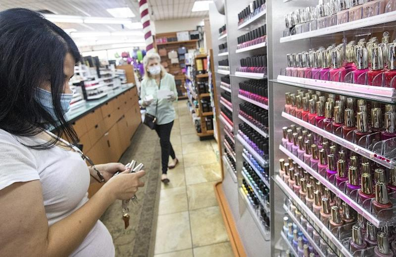 """SHER MAN OAKS, CA-MAY 15, 2020: Jaqueline Argelagos of Sherman Oaks, left, wearing a protective mask against the coronavirus, shops for nail polish inside Sherman Oaks Beauty Collection. The store is one of 60 non-essential businesses cited by Los Angeles City Attorney Mike Feuer for """"flouting the city's Safer at Home order. Store owner Janet Tavakoli says she shut down her store for 2 weeks, losing $15,000 in sales but reopened after seeing beauty store competitors open. (Mel Melcon/Los Angeles Times)"""
