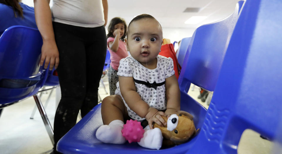 An immigrant infant plays with a stuffed animal inside the Catholic Charities of the Rio Grande Valley on Saturday, June 23, 2018, in McAllen, Texas. Families, who have been processed and released by U.S. Customs and Border Protection, wait inside the facility before continuing their journey to cities across the United States. (AP Photo/David J. Phillip)