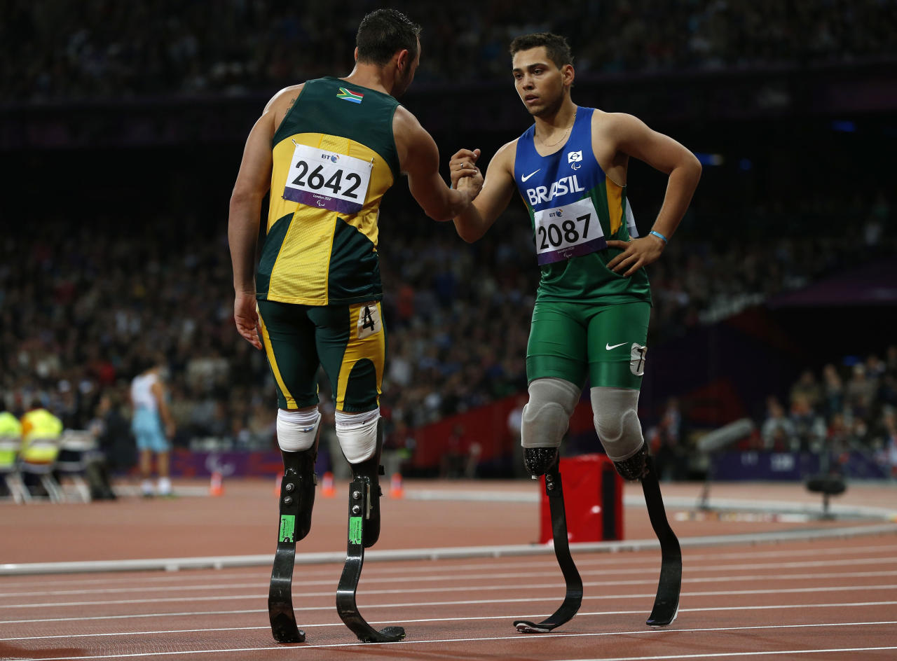 Brazil's Alan Oliveira (R) is congratulated by South Africa's Oscar Pistorius after winning the men's 200m T44 classification at the Olympic Stadium during the London 2012 Paralympic Games September 2, 2012. This classification is for athletes with an impairment that affects their arms or legs, including amputees.     REUTERS/Eddie Keogh (BRITAIN - Tags: SPORT ATHLETICS OLYMPICS) - RTR37F1Y