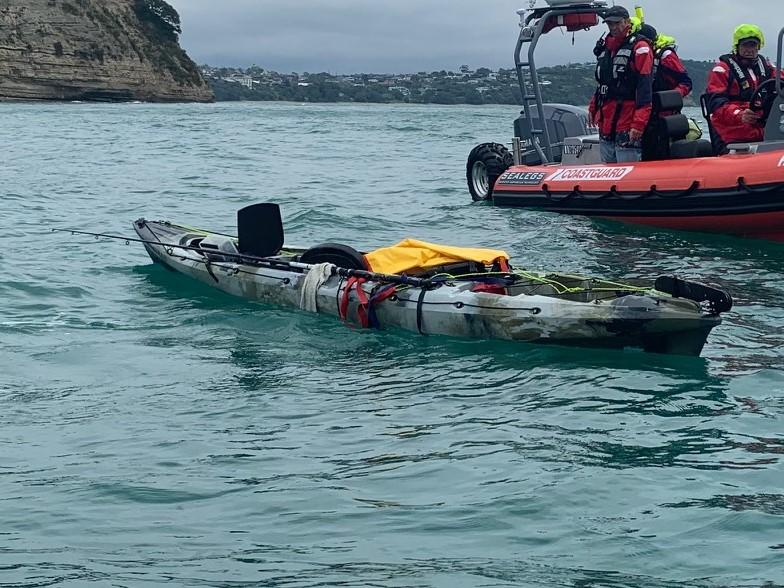 A fishing kayak is seen with the coast guard inspecting it in waters off Whangaparaoa.