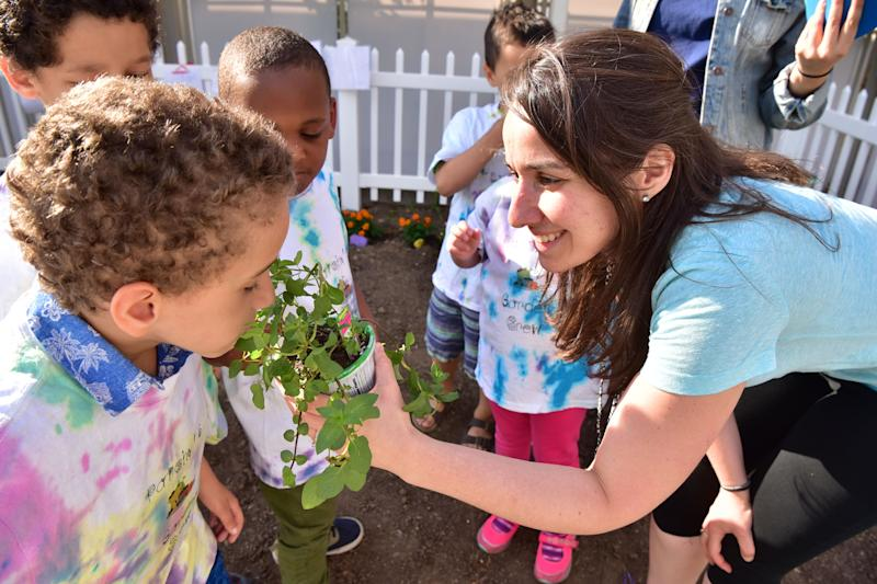 20029124A Kathleen Moran of the Binder Autism Center offers the smell of a mint chocolate plant to Alex Camilo at the garden of St. Joseph's Wayne Hospital on Tuesday. Binder Autism Center clinicians are using gardening as the vehicle to teach and practice social skills to children affected with autism