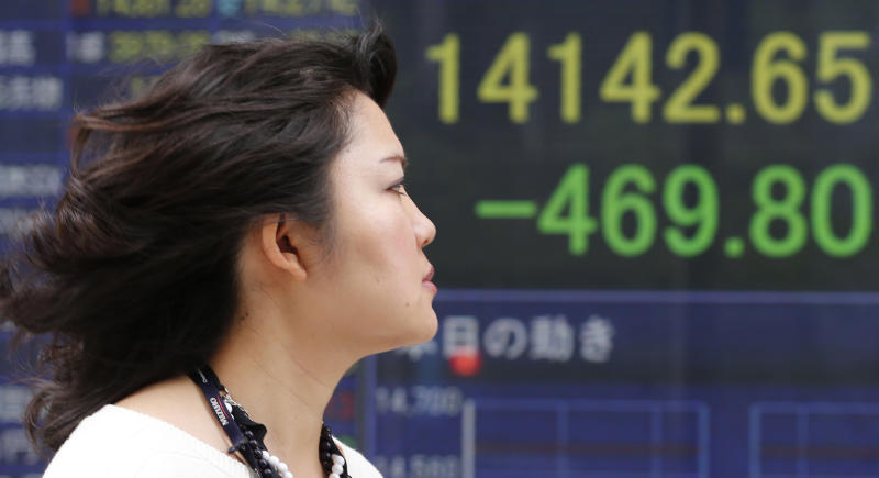A woman walks by an electronic stock board of a securities firm in Tokyo Monday, May 27, 2013. The Nikkei 225 closed down 469.80 points, or 3.22 percent at 14,142.65 Monday after the yen reversed some of its recent fall against the U.S. dollar. Stocks elsewhere in Asia were mixed as investors tried to sort out conflicting indicators about the health of the global economy. (AP Photo/Koji Sasahara)
