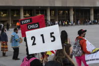 People form a circle during a vigil in Toronto on Sunday May 30, 2021, for the 215 Indigenous children, whose remains were uncovered on the grounds of a former residential school near Kamloops, British Columbia. The discovery of a mass grave was announced late on Thursday by the Tk'emlups te Secwépemc people after the site was examined by a team using ground-penetrating radar. (Chris Young/The Canadian Press via AP)