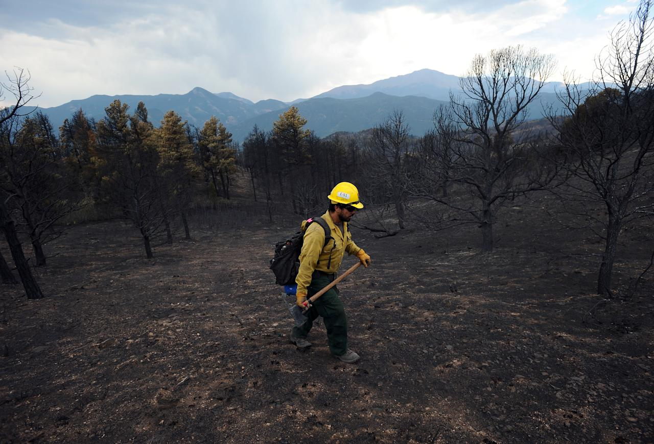 """A firefighter from King Canyon National Park in California walks through a burned-out area of Colorado Springs, Colo., Friday, June 29, 2012. After declaring a """"major disaster"""" in the state early Friday and promising federal aid, President Barack Obama got a firsthand view of the wildfires and their toll on residential communities. More than 30,000 people have been evacuated in what is now the most destructive wildfire in state history. (AP Photo/The Gazette, Christian Murdock)"""