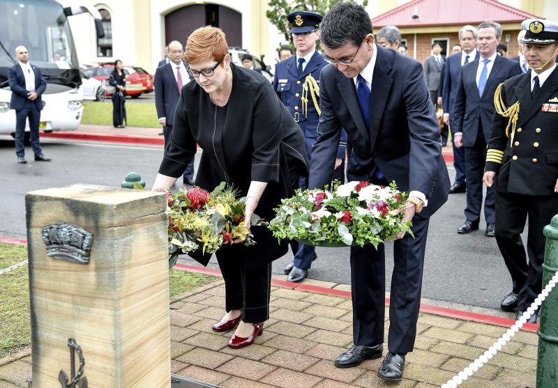 Japanese Foreign Minister Taro Kono, right, and Australian Foreign Minister Marise Payne lay wreaths at HMAS Kuttabul in Sydney, Wednesday, Oct. 10, 2018. Australia and Japan on Wednesday reaffirmed their commitment to pressuring North Korea to abandon its nuclear weapons program and enforcing sanctions on Pyongyang. (Brendan Esposito/AAP Images via AP)