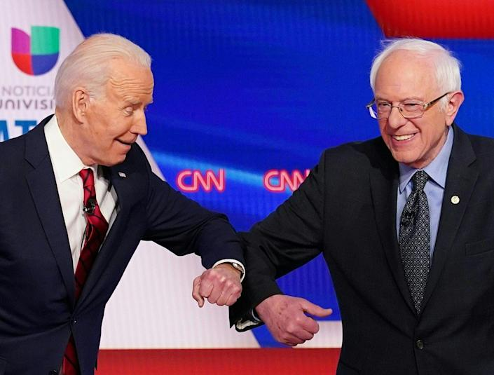 Presidential hopefuls Joe Biden and Bernie Sanders greet each other with an elbow bump at a Democratic debate on March 15. (Mandel Ngan/AFP via Getty Images)