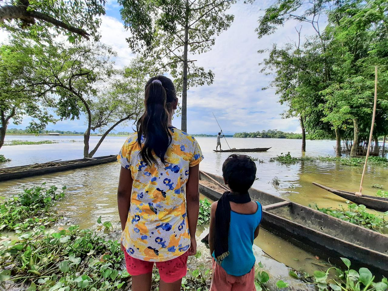 Two girls of Laibil village in Sibsagar district watches increase level of the water due to heavy rain in Sibsagar district of Assam, India, on July 22, 2020. .Many villages have been affected due to flood more than 500 families have been affected till July according to the report. (Photo by Dimpy Gogoi/NurPhoto via Getty Images)