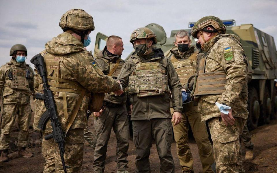 Ukraine's President Volodymyr Zelenskiy (c) shakes hands with soldiers on the frontline - AFP
