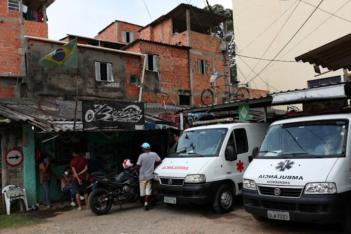 People gather next to ambulances on March 29, 2020, after residents of São Paulo's biggest favela, Paraisópolis, hired an around-the-clock private medical service to fight COVID-19. (Photo: Amanda Perobelli / Reuters)