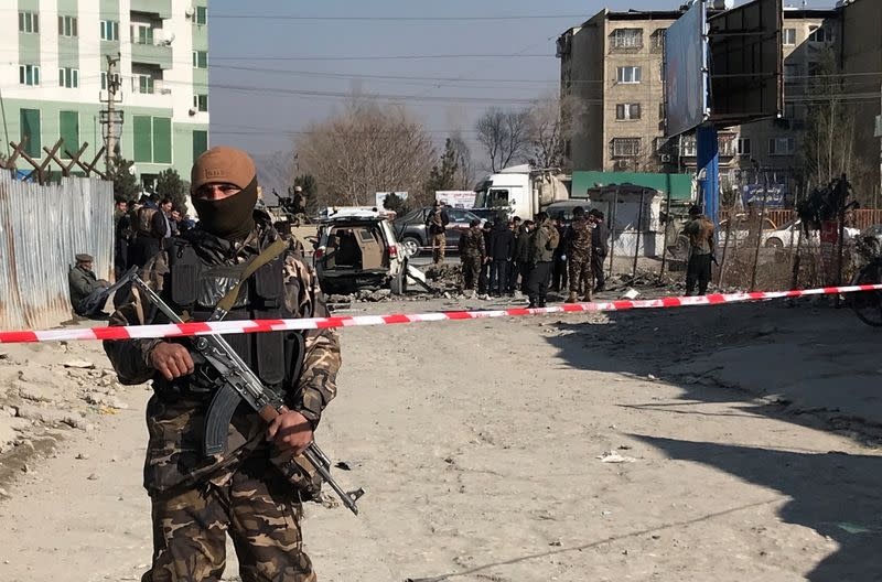 An Afghan security officer keeps watch at the site of a blast in Kabul