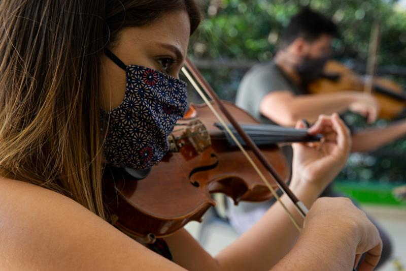SAO PAULO, BRAZIL - JUNE 25: A Baccarelli Institute student plays the violin during the distribution of food at the institute's headquarters in Heliopolis amidst the coronavirus pandemic on June 25, 2020 in Sao Paulo, Brazil. Instituto Baccarelli is a non-profit organization that teaches music to more than 1200 underprivileged and socially vulnerable children and young people in Heliopolis, one of the biggest favelas in Sao Paulo of over 200,000 inhabitants. The Institute is responsible for creating the first orchestra in the world that emerged in a favela, the Heliopolis Symphonic Orchestra. With the social and economic impact of the coronavirus (COVID-19) pandemic in these poor communities, Instituto Baccarelli decided to raise funds and the donations are used for food, cleaning and hygiene products. (Photo by Alexandre Schneider/Getty Images)