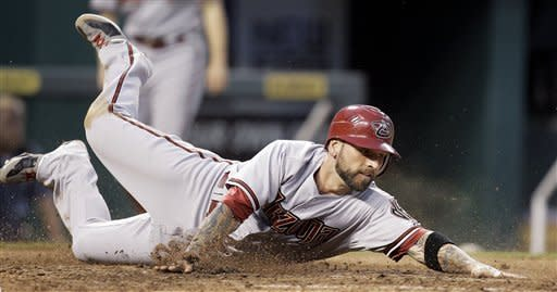 Arizona Diamondbacks' Ryan Roberts slides home to score after Aaron Hill hit into a double play during the seventh inning of a baseball game against the Kansas City Royals on Saturday, May 19, 2012, in Kansas City, Mo. (AP Photo/Charlie Riedel)