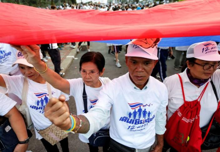 Supporters of Thailand's Prime Minister Prayut Chan-o-cha walk to show their support for the government at a park in Bangkok