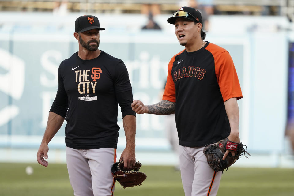 San Francisco Giants manager Gabe Kapler, left, talks with third baseman Wilmer Flores, right, during batting practice before Game 3 of a baseball National League Division Series against the Los Angeles Dodgers, Monday, Oct. 11, 2021, in Los Angeles. (AP Photo/Marcio Sanchez)