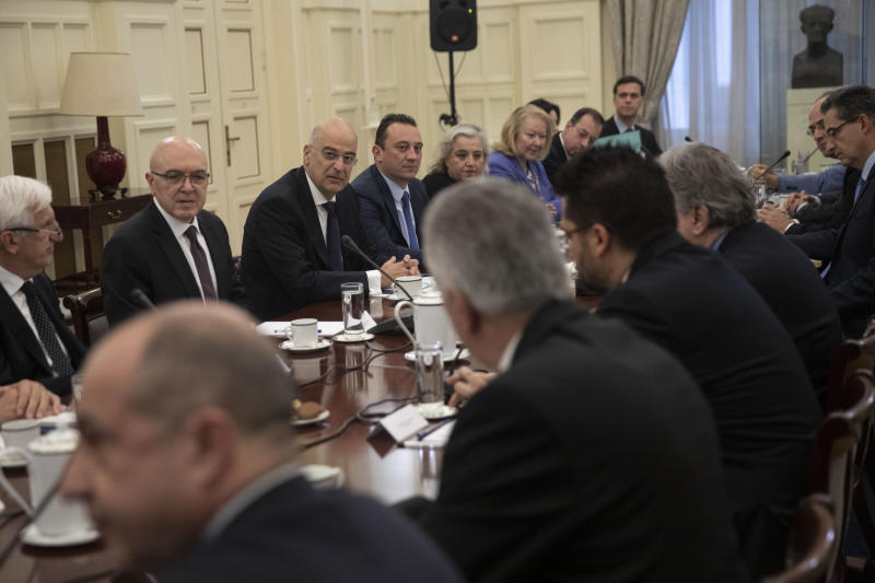 Greek foreign Minister Nikos Dendias, facing third left, takes part in a meeting with political party representatives on developments for the maritime boundary deal between Turkey and Libya in Athens, on Tuesday, Dec. 10, 2019. Greece has sent two letters to the United Nations explaining its objections to the deal and asking for the matter to be taken up by the U.N. Security Council, the government spokesman said Tuesday. (AP Photo/Petros Giannakouris)