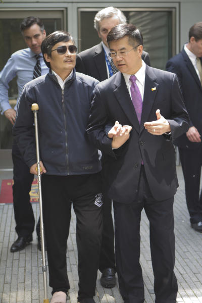 In this photo released by the US Embassy Beijing Press Office, blind lawyer Chen Guangcheng, left, chats with U.S. ambassador to China, Gary Locke as they leave the U.S. embassy for a hospital in Beijing, Wednesday, May 2, 2012. (AP Photo/U.S. Embassy Beijing Press Office, HO)