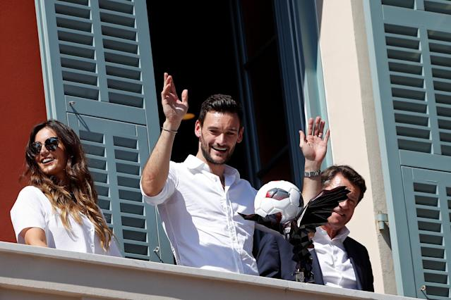 France soccer team goalkeeper Hugo Lloris surrounded by his wife Marine, and Christian Estrosi, Mayor of Nice, holds a trophy with an eagle, the city's emblem, from a balcony at the city hall in Nice, after their victory in the 2018 Russia Soccer World Cup, in Nice, France, July 18, 2018. REUTERS/Eric Gaillard