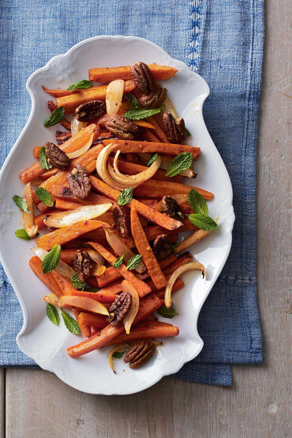 "<p>Fresh mint brings a bright note to hearty root vegetables garnished with spiced pecans. </p><p><strong>Tip:</strong> Coated in orange juice and spices—in addition to the usual oil—will make this sweet potato, carrot, and onion mix pop with flavor.</p><p><strong><a href=""https://www.countryliving.com/food-drinks/recipes/a5079/roasted-sweet-potatoes-carrots-recipe-clx1113/"" rel=""nofollow noopener"" target=""_blank"" data-ylk=""slk:Get the recipe"" class=""link rapid-noclick-resp"">Get the recipe</a>.</strong></p>"