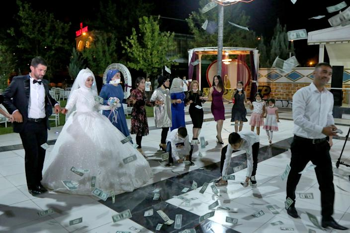 Groom Serdal Aman and bride Filiz Peker dance with their relatives during their wedding after Turkey lifted restrictions on the ceremonies which had been imposed to prevent the spread of the coronavirus disease (COVID-19), in Diyarbakir, Turkey, July 1, 2020. REUTERS/Sertac Kayar