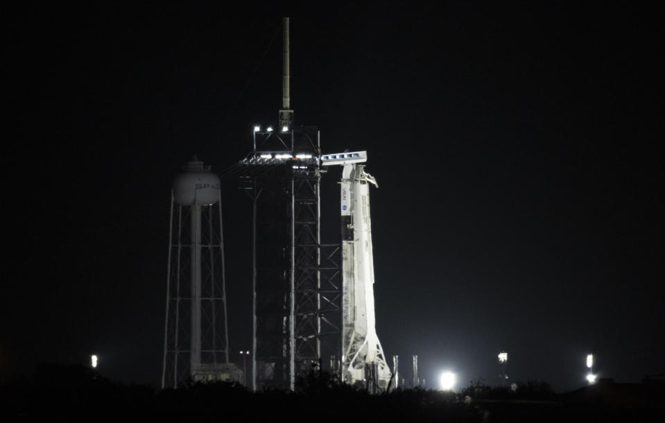 A SpaceX rocket with the company's Dragon capsule is illuminated by spotlights on the launch pad, early Friday, April 23, 2021, at NASA's Kennedy Space Center in Cape Canaveral, Fla. SpaceX aimed to launch its third crew a little before sunrise Friday, this time using a recycled capsule and rocket. The four astronauts, representing the U.S., Japan and France, were supposed to fly to the International Space Station on Thursday. But liftoff was delayed because of poor weather offshore. (Joel Kowsky/NASA via AP)