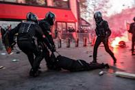 Police officers drag a man along the ground during Saturday's protest in Paris. The draft law that sparked the demonstration would restrict the filming of police