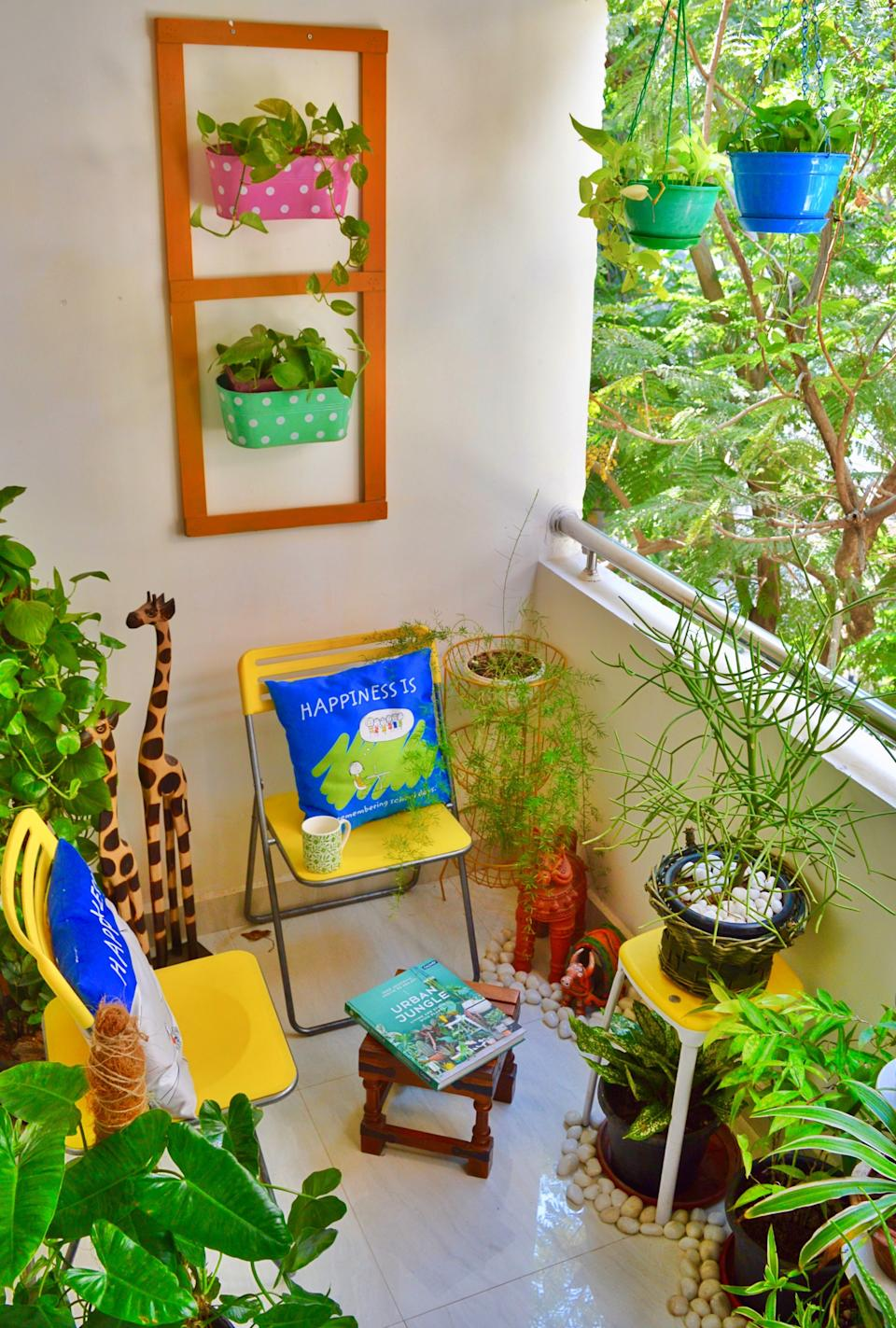 The cosy balcony garden accommodates a sit-out space. The tiered plant-holder in the far corner is a repurposed vegetable storage unit and the wooden wall frame has been upcycled from packing material.