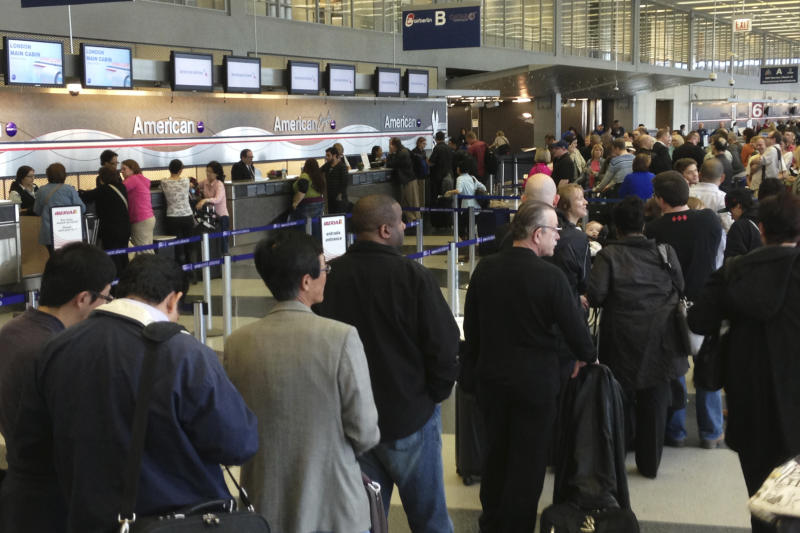In this cell phone image, passengers are lined up at the American Airlines ticket counters at Chicago's O'Hare International Airport Tuesday, April 16, 2013. American Airlines says it has fixed an outage in its main reservations system that is disrupting travel for thousands of passengers whose flights have been delayed or canceled. Roughly 900 flights are directly impacted, according to flight tracking site FlightAware, with another 800 indirectly impacted due to planes and crew being out of place. (AP Photo/Bob Brant)