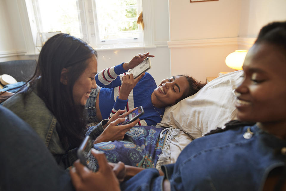 Smiling young female friends enjoying slumber party while using smart phones on bed at home