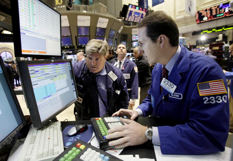 In this Nov. 11, 2010 photo, specialist Glenn Carell, right, works at his post on the floor of the New York Stock Exchange. (AP Photo/Richard Drew)
