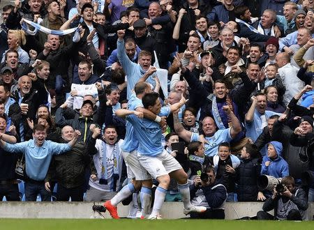 """Manchester City's Samir Nasri (R) is congratulated by teammate Pablo Zabaleta after scoring against West Ham United during their English Premier League soccer match at the Etihad Stadium in Manchester, northern England May 11, 2014. REUTERS/Nigel Roddis (BRITAIN - Tags: SPORT SOCCER) FOR EDITORIAL USE ONLY. NOT FOR SALE FOR MARKETING OR ADVERTISING CAMPAIGNS. NO USE WITH UNAUTHORIZED AUDIO, VIDEO, DATA, FIXTURE LISTS, CLUB/LEAGUE LOGOS OR """"LIVE"""" SERVICES. ONLINE IN-MATCH USE LIMITED TO 45 IMAGES, NO VIDEO EMULATION. NO USE IN BETTING, GAMES OR SINGLE CLUB/LEAGUE/PLAYER PUBLICATIONS - RTR3OO23"""