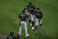 Cleveland Indians' Eddie Rosario right, celebrates with teammates Amed Rosario (1) and Franmil Reyes back, after Eddie Rosario hit a two-run home run during the second inning of a baseball game against the Chicago White Sox Monday, April 12, 2021, in Chicago. (AP Photo/Paul Beaty)