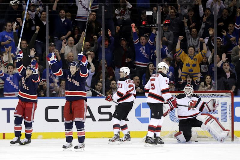 New York Rangers' Derek Stepan, second from left, celebrates his goal with Ryane Clowe, left, while New Jersey Devils' Andrei Loktionov, center, Adam Larsson, second form right, and goalie Martin Brodeur look on during the first period of an NHL hockey game, Sunday, April 21, 2013, in New York. (AP Photo/Seth Wenig)