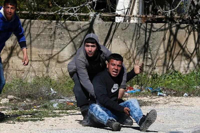 An injured young Palestinian man is helped at the Amari Palestinian refugee camp, near the West Bank city of Ramallah, during clashes with Israeli soldiers on February 15, 2016 (AFP Photo/Abbas Momani)