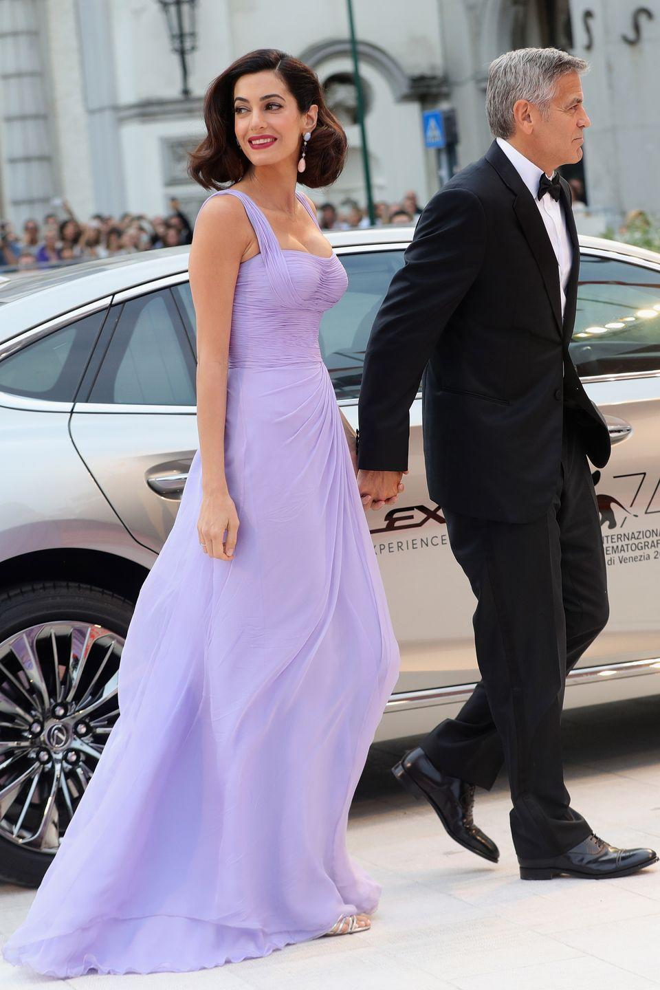 <p>Amal Clooney walked the red carpet at the Venice Film Festival in 2017 wearing a flowing lavender gown by Atelier Versace that immediately reminded us of Meg's signature look.</p>