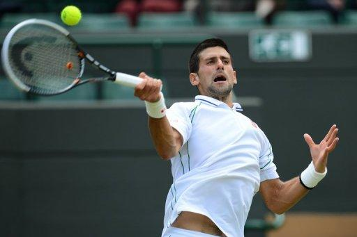 Serbia's Novak Djokovic plays a forehand shot during his men's singles quarter-final victory over Germany's Florian Mayerat Wimbledon on Wednesday. Defending champion Djokovic and six-time winner Roger Federer face a titanic Wimbledon semi-final showdown after the two title contenders wasted little time on their last eight matches on Wednesday