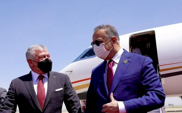 A photo released by the Iraqi Prime Minister Media Office shows Iraqi Prime Minister Mustafa al-Kadhimi, right, as he welcomes Jordan's King Abdullah II before the Baghdad Conference for Cooperation and Partnership in Baghdad, Saturday, Aug. 28, 2021. (Iraqi Prime Minister Media Office, via AP)