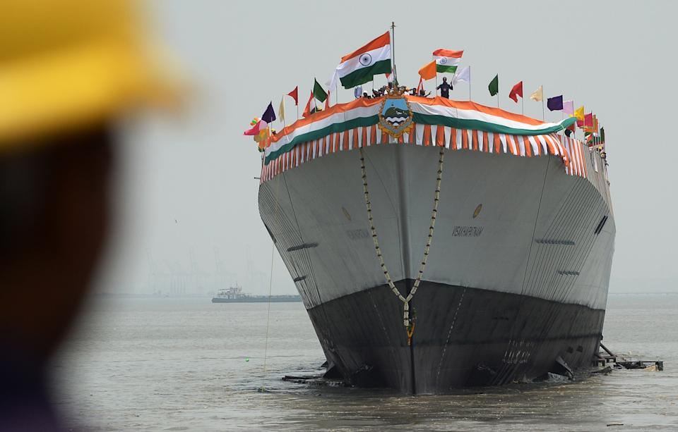 An Indian worker watches as INS Visakhapatnam, the first Indian Navy P15-B stealth destroyer, is launched in Mumbai on April 20, 2015. The indigenously-designed ships air defence capability is designed to counter the threat of enemy aircraft and anti-ship cruise missiles, and will revolve around a vertical launch and long-range surface-to-air missile system. The vessel is expected to be commissioned into the India Navy in 2018.  AFP PHOTO/ Indranil MUKHERJEE        (Photo credit should read INDRANIL MUKHERJEE/AFP via Getty Images)
