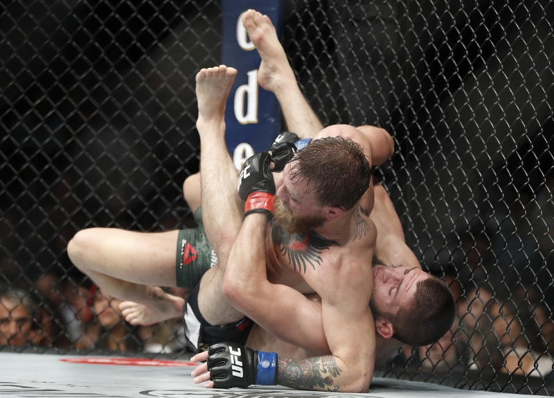 Khabib Nurmagomedov, right, takes down Conor McGregor during a lightweight title mixed martial arts bout at UFC 229 in Las Vegas, Saturday, Oct. 6, 2018. Nurmagomedov won the fight by submission during the fourth round to retain the title. (AP Photo/John Locher)