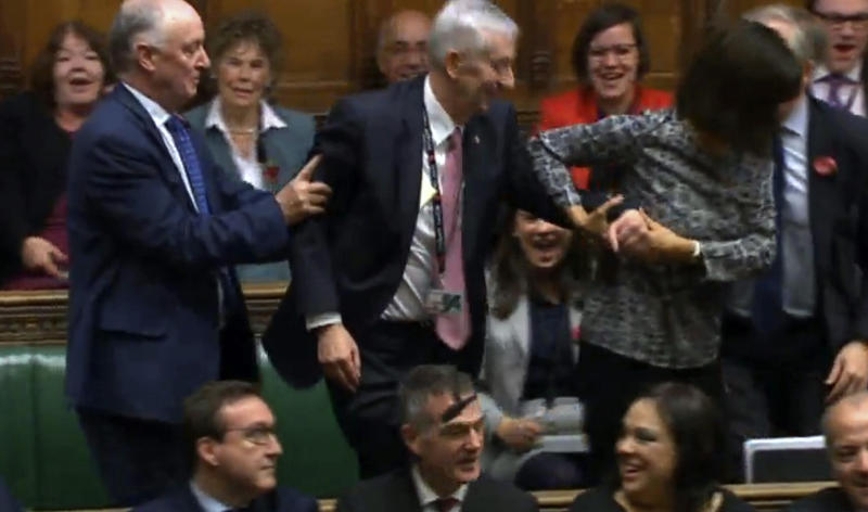 In this image made from video, Lindsay Hoyle, center, is dragged to the speaker's chair after being voted the new Speaker of the House of Commons, in London, Monday, Nov. 4, 2019. Long-serving Labour Party lawmaker Lindsay Hoyle has been elected the new speaker of Britain's House of Commons. He succeeds the influential but divisive John Bercow. The 62-year-old legislator won 325 of 540 votes cast by lawmakers in a final round of voting on Monday. (House of Commons via AP)