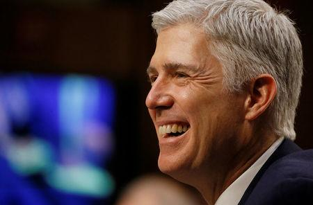 FILE PHOTO: U.S. Supreme Court nominee judge Neil Gorsuch smiles in reaction to a question as he testifies during the third day of his Senate Judiciary Committee confirmation hearing on Capitol Hill in Washington, U.S. on March 22, 2017. REUTERS/Jim Bourg/File Photo