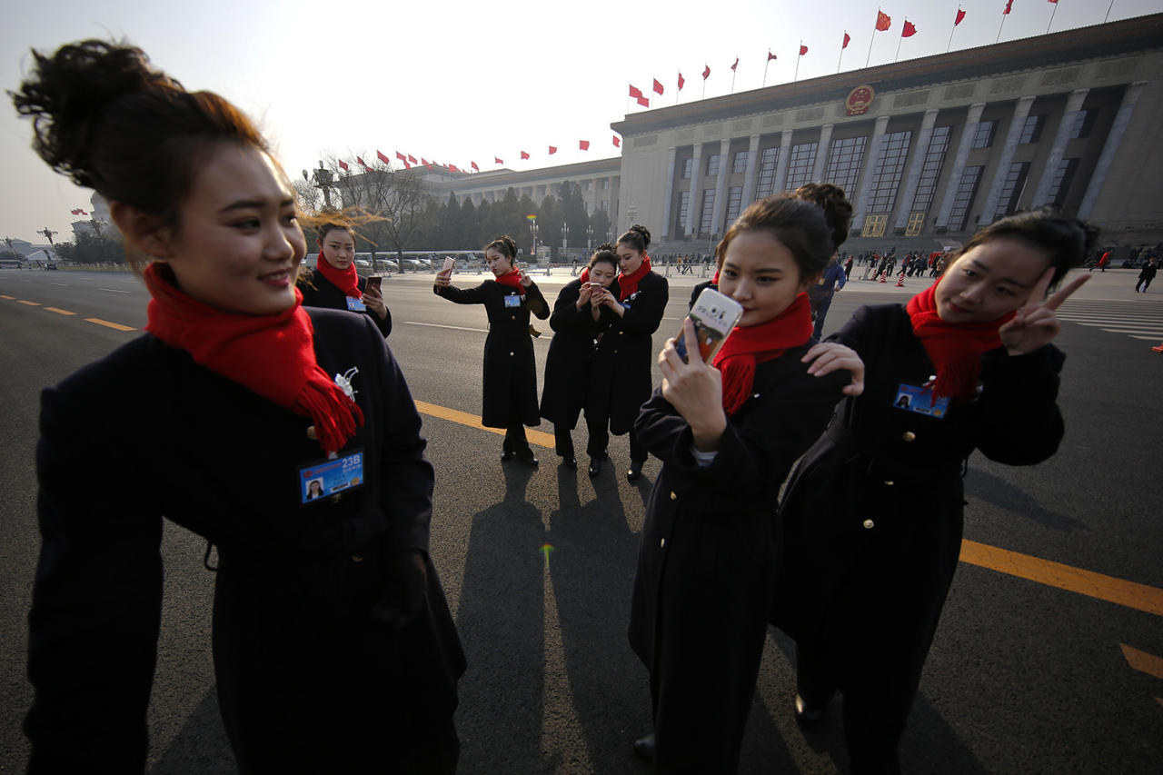 <p>Bus ushers take selfies on an empty street adjacent to the Great Hall of the People during the Chinese People's Political Consultative Conference (CPPCC) in Beijing, Friday, March 3, 2017. Thousands of delegates have gathered at the Chinese capital for the opening of the annual session of the Chinese People's Political Consultative Conference, which advises the rubberstamp parliament, whose annual session begins Sunday. (AP Photo/Andy Wong) </p>